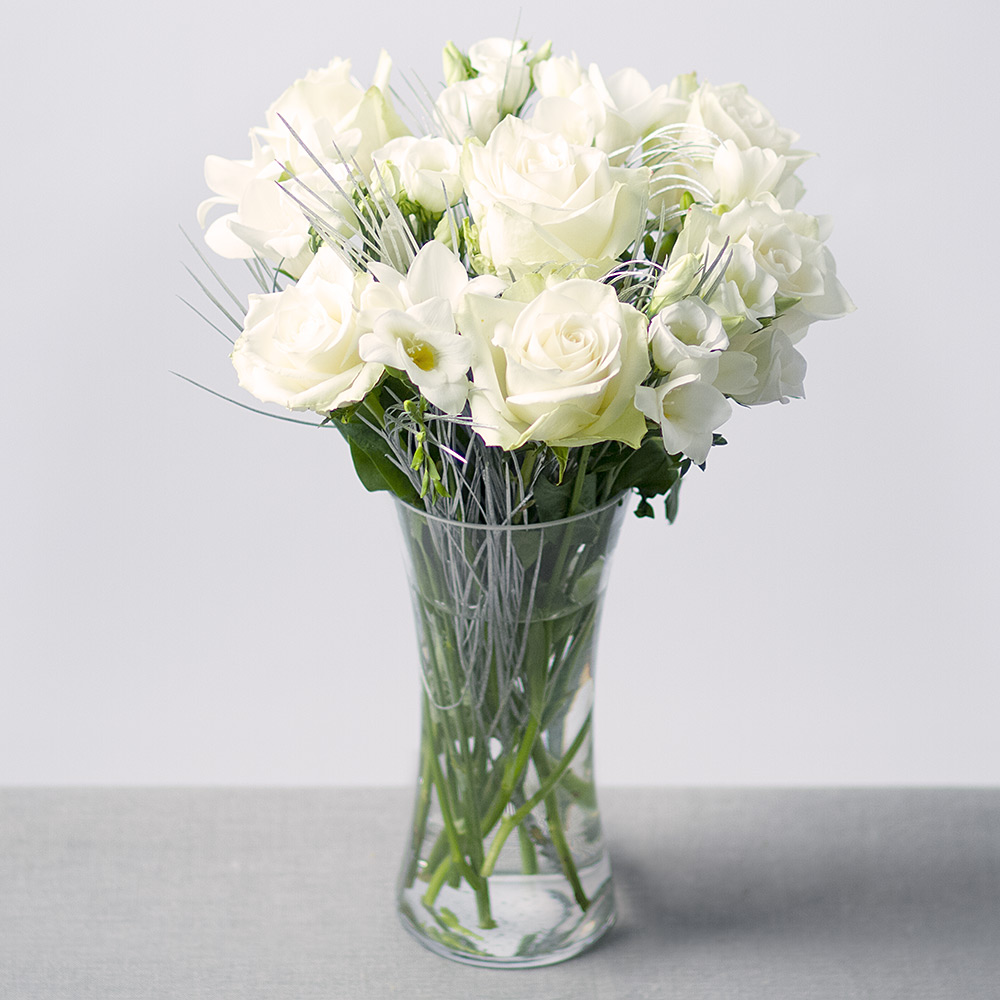 Image of A beautiful display of white Athena Roses, Freesias and Lisianthus with silver Grevillea leaves providing the perfect finishing touch.