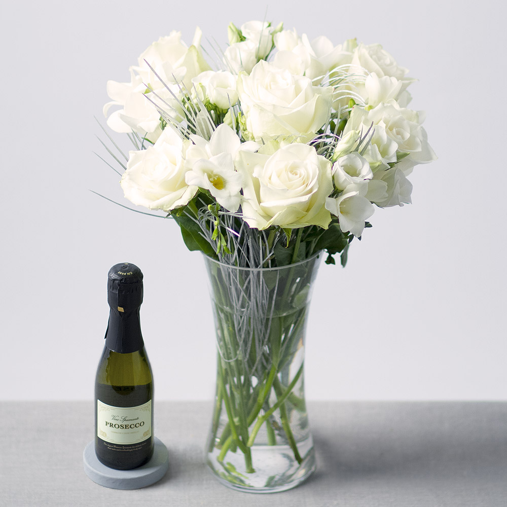 Image of A beautiful display of white Athena Roses, Freesias and Lisianthus with silver Grevillea leaves providing the perfect finishing touch.Delivered with a 20cl bottle of Vino Spumante Prosecco.