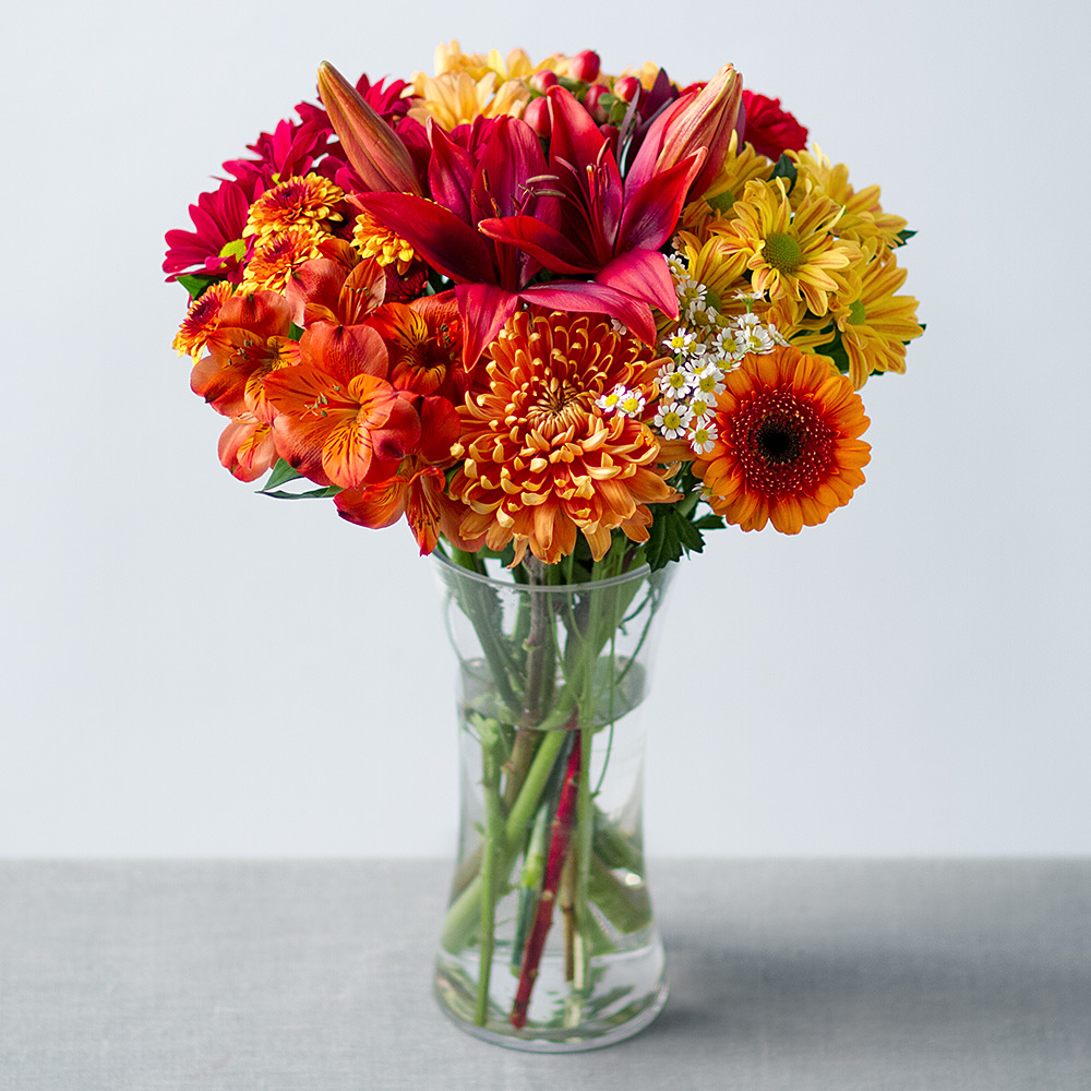 Image of A unique and showy orange Leucadendron, stunning red Asiatic Lily and bright orange Germini are the focus of this autumn-themed bouquet.Alstroemeria, Matricaria, Hypericum Berries and a selection of Chrysanthemums in autumn shades of yellow, orange and red make this the perfect seasonal display.