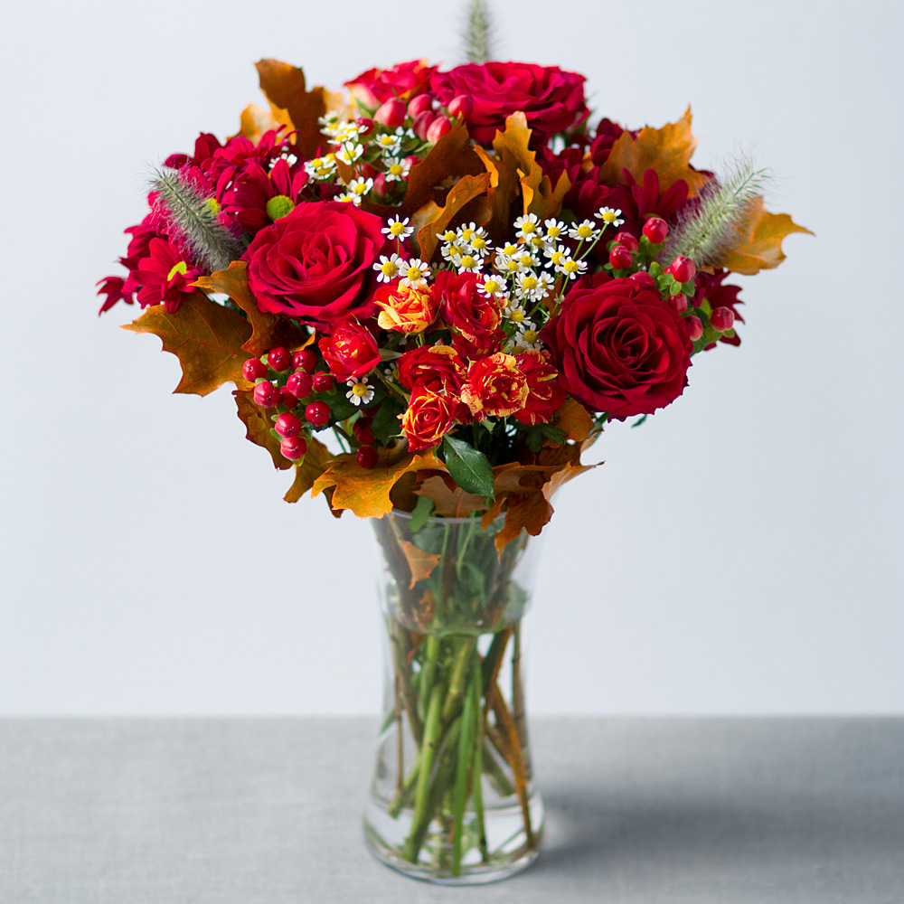 Image of A beautiful autumnal arrangement featuring 'Upper Class' red Roses, two-tone Spray Roses with red Chrysanthemums.Hypericum Berries and  Oak leaves give the display a lovely final touch.