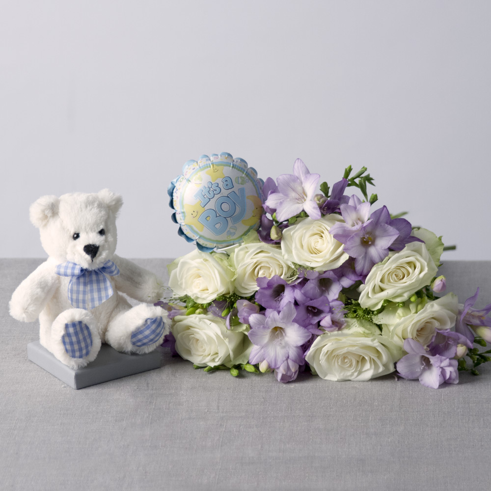 Image of Celebrate the arrival of a new born baby boy with our new baby boy gift, including a beautiful bouquet for mum, a fun 'It's a Boy' mini balloon and an adorable teddy for baby.A delightful collection of pure white Roses and lovely lilac Freesias accompanied by stems of Panicum grass.