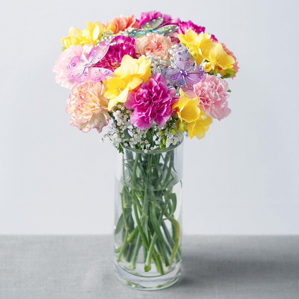 Image of Carnations in mixed colours of cerise, orange, yellow and pink are joined by pretty yellow Freesia.Gentle white Gypsophila and three fun keepsake butterfly picks complete this charming arrangement.