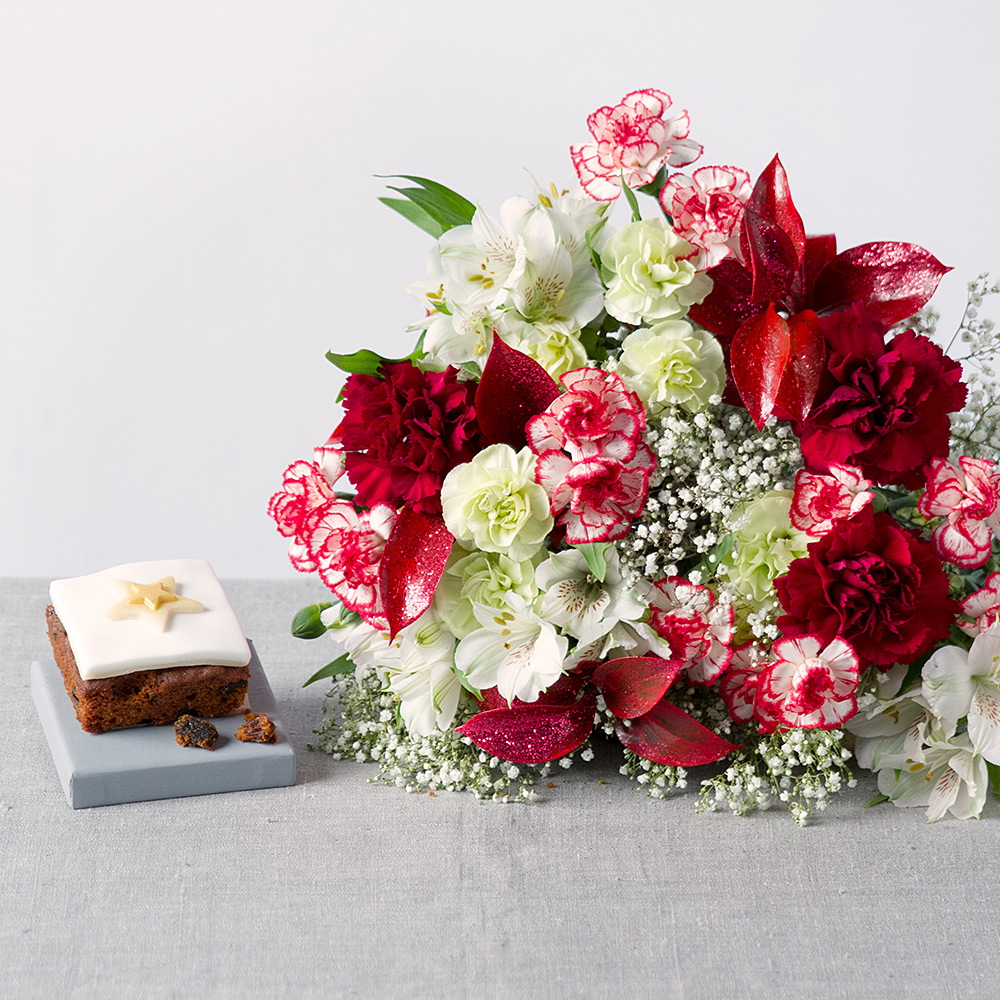 Image of This long-lasting Christmas bouquet contains mixed Spray Carnations, white Alstroemeria, Gypsophila and red glitter Ruscus.A delicious miniature Christmas iced fruit cake completes the gift.