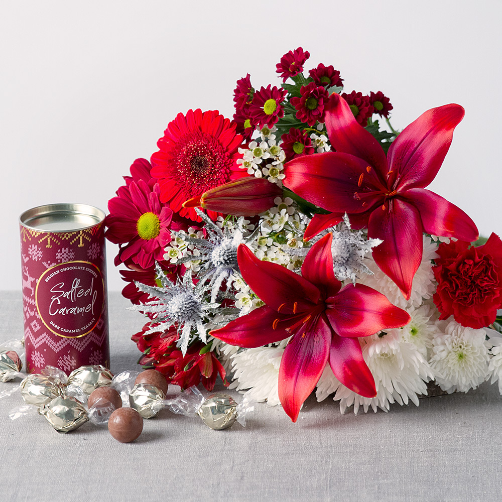 Image of A striking red and white bouquet featuring red Asiatic Lily, Germini, Carnations and Chrysanthemums with white Wax Flower and snow-dusted thistle.A delicious 110g tin of dark chocolate covered salted caramels make the gift extra special.