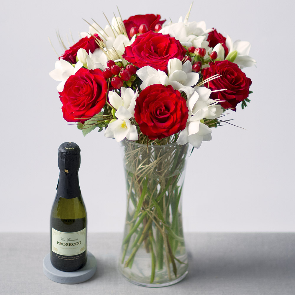 Image of Red Roses and white Freesias with gold Grevillea leaves and red Hypericum Berries delivered with a 20cl bottle of Prosecco.