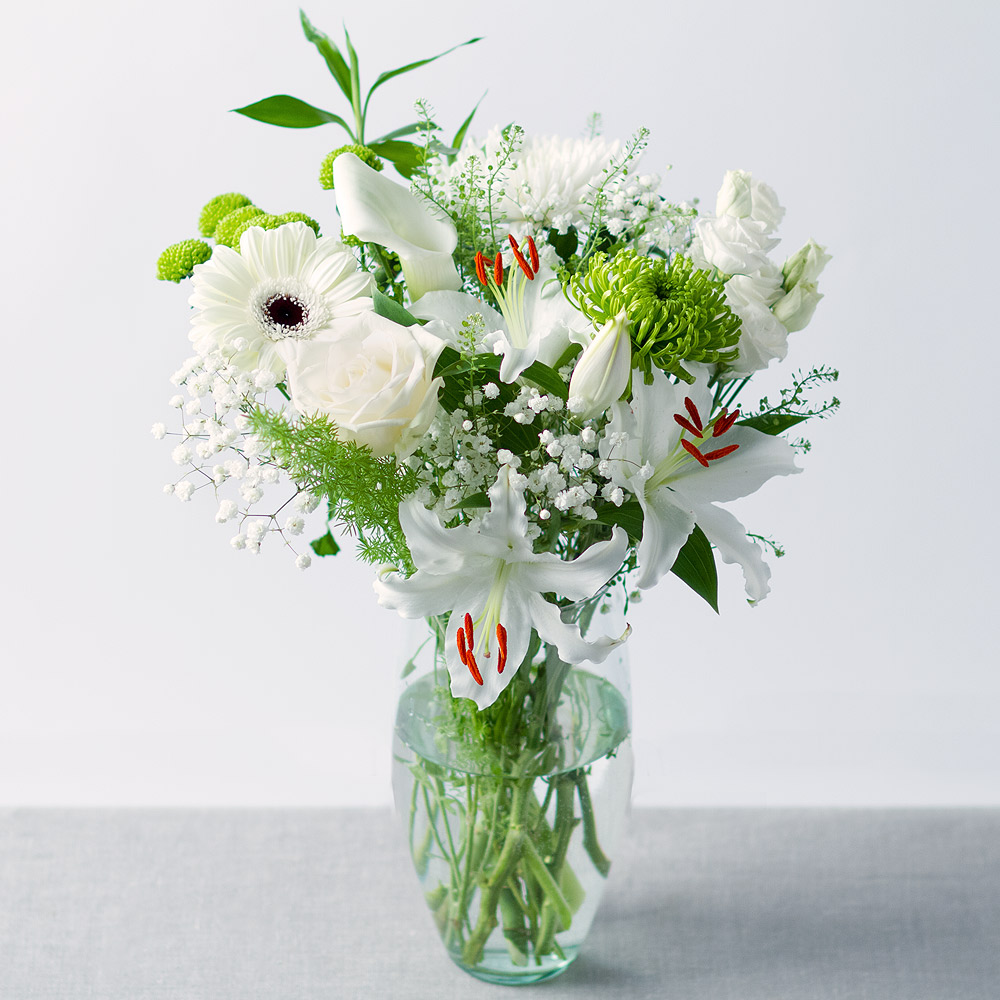 Image of A selection of attractive white blooms feature in this springtime bouquet, with a stunning white Rose and two elegant Lilies providing the main focus.Green Chrysanthemum and an array of complementing greenery provide a wonderful contrast.