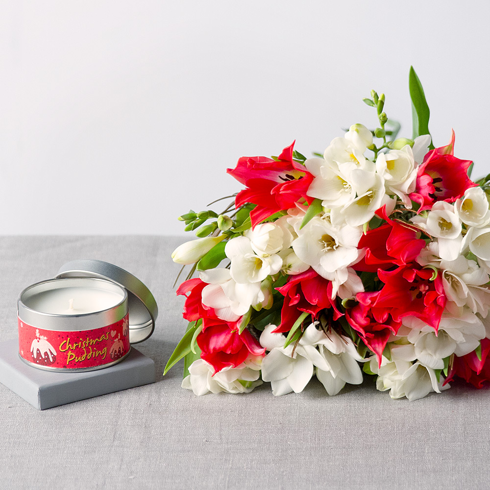 Image of A gorgeous Christmas gift to send to someone special.Tulips and Freesias in colours of red & white are joined by a luxurious Christmas scented candle.