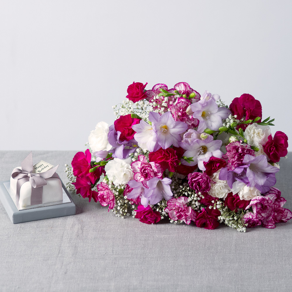 Image of A beautiful birthday gift featuring a charming flower arrangement and a delicious miniature birthday cake.Lilac Freesias are joined by a delightful mix of purple, white and purple-edged Spray Carnations and white Gypsophila provides the perfect finishing touch.