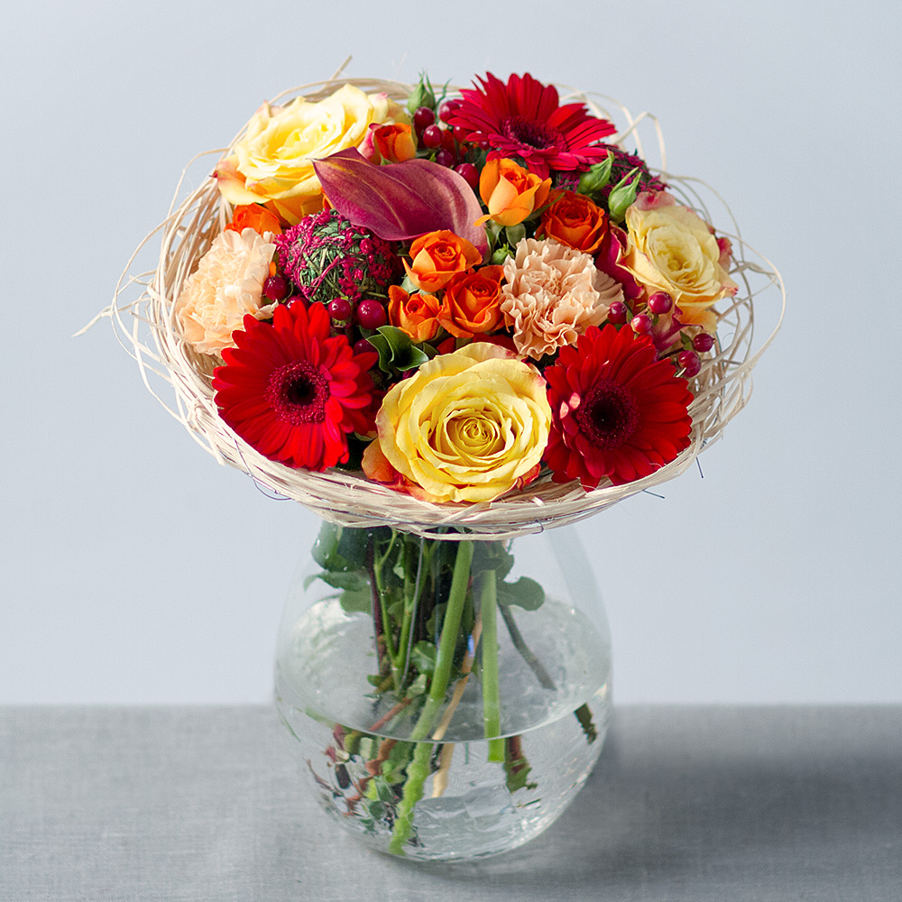 Image of A magnificent rustic bouquet in eye-catching colours of dark red, deep orange and golden yellow.Featuring Calla Lily, Roses, Germini and Carnations with Hypericum Berries and greenery presented in a straw holder, it is ready to display upon arrival.