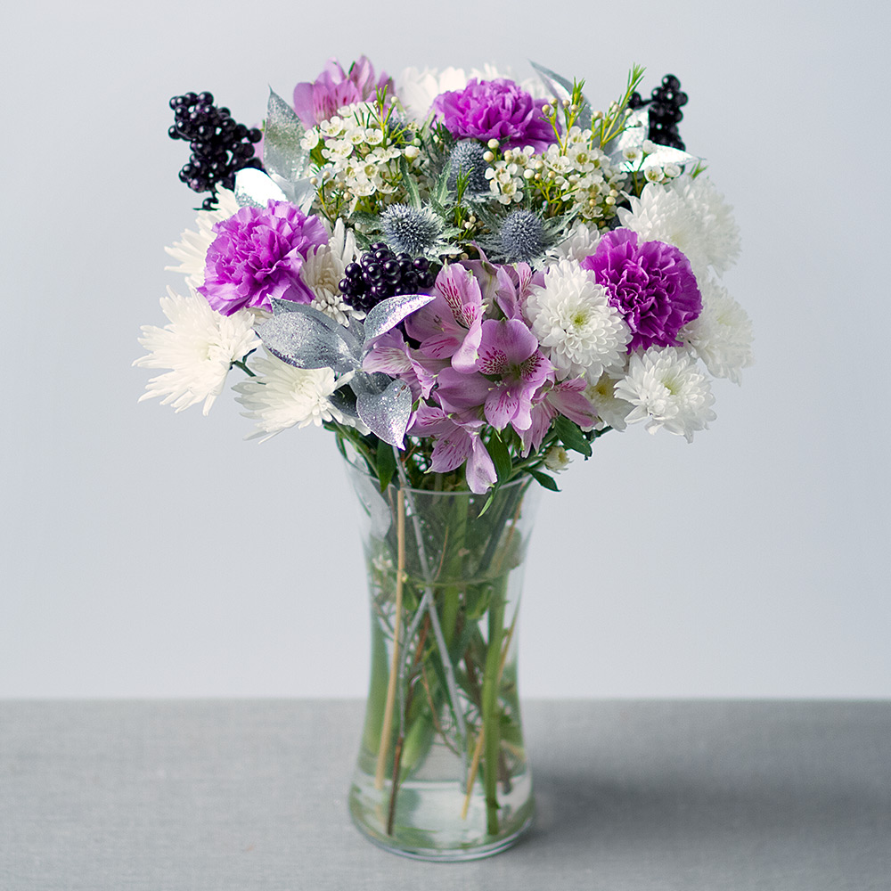 Image of This bouquet includes purple Alstroemeria, lilac Carnations, mixed Chrysanthemums and white Wax Flower. Snow-dusted Thistle, glittered silver Ruscus and purple berry decorations provide the finishing touch.