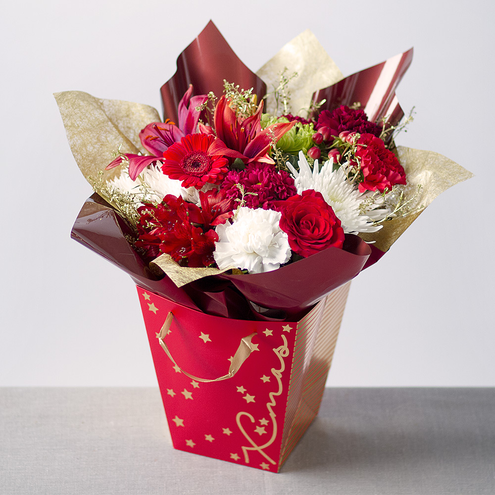 Image of A Christmas gift bag featuring a red Rose, Germini and Asiatic Lily with Carnations and Chrysanthemums in red, white and green.A spray of red Hypericum Berries and gold Green Bell foliage complete the gift, which is ready arranged to create an instant display.