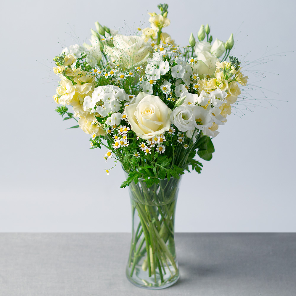 Image of An array of wonderful white Roses, Phlox and Freesia are joined by cream Stocks and daisy-like Matricaria.Alchemilla greenery provides a wonderful finish to this bubbly, summer display.