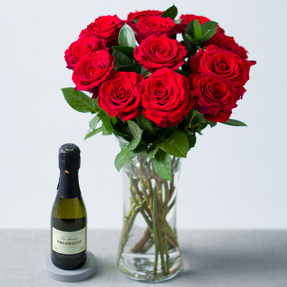 Image of 12 elegant Upper Class red Roses are beautifully complemented with glossy deep green Ruscus leaves.Delivered with a 20cl bottle of Prosecco.