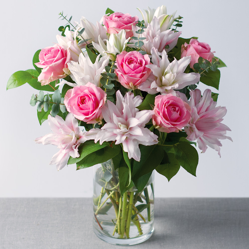 Image of A stunning arrangement of pink Wham Roses feature alongside exquisite L'or du Roselily Isabella lilies.Finished with an array of Salal leaves and baby blue eucalyptus, it creates an eye-catching display.The L'or du Roselily Isabella can be found exclusively to Bunches. A double-headed variety, this Lily has hidden stamen, removing the risk of pollen stains commonly found with other Lilies.