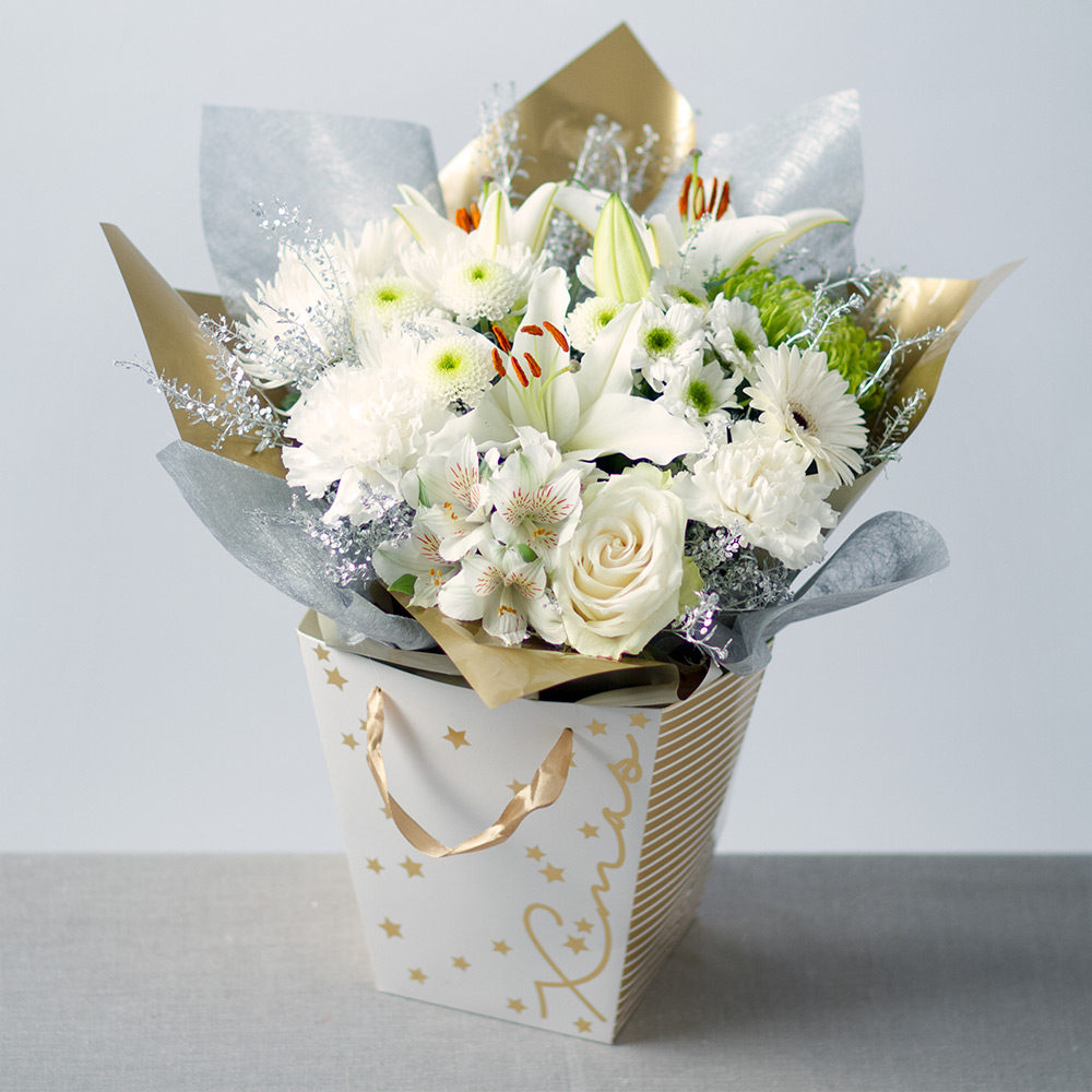 Image of A white Oriental Lily is accompanied by Alstroemeria, Carnations and Chrysanthemums in Christmas colours of white and green.Silver Green Bell foliage provides the perfect finish to this seasonal gift bag which provides an instant display for the recipient.