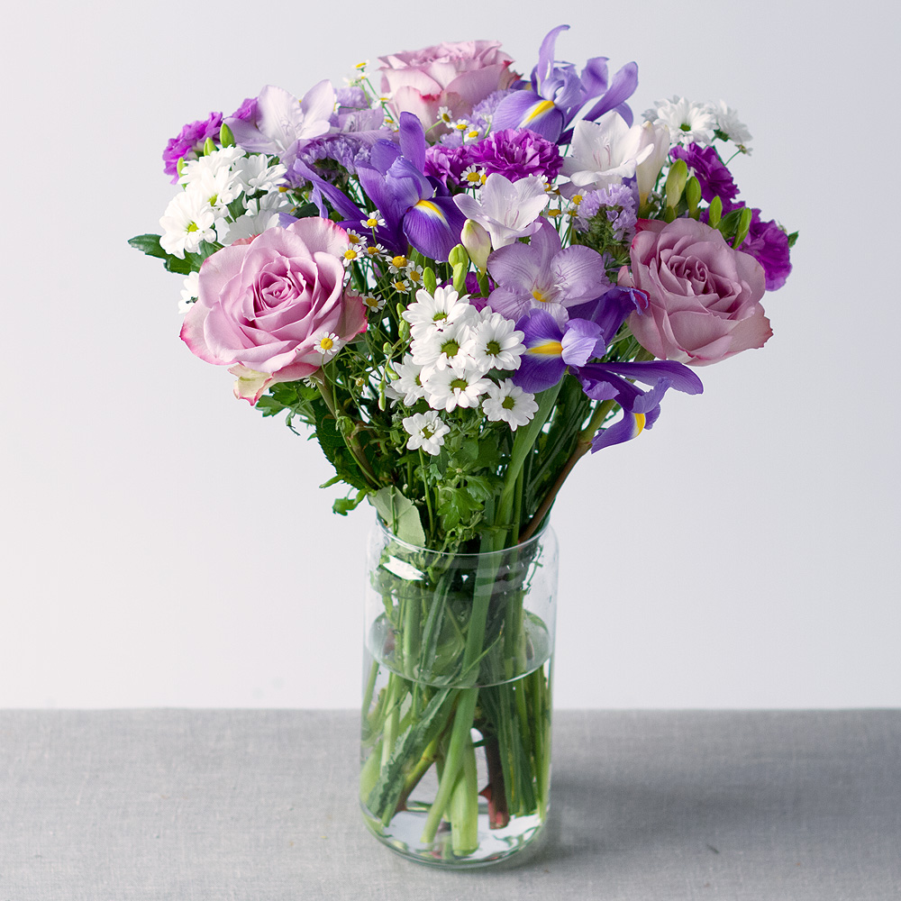 Image of Beautiful blue Iris, lavender Roses and white Chrysanthemums feature in this fresh, spring inspired bouquet.Lavender Freesias and Statice along with sprays of Matricaria Daisies help to complete the look!