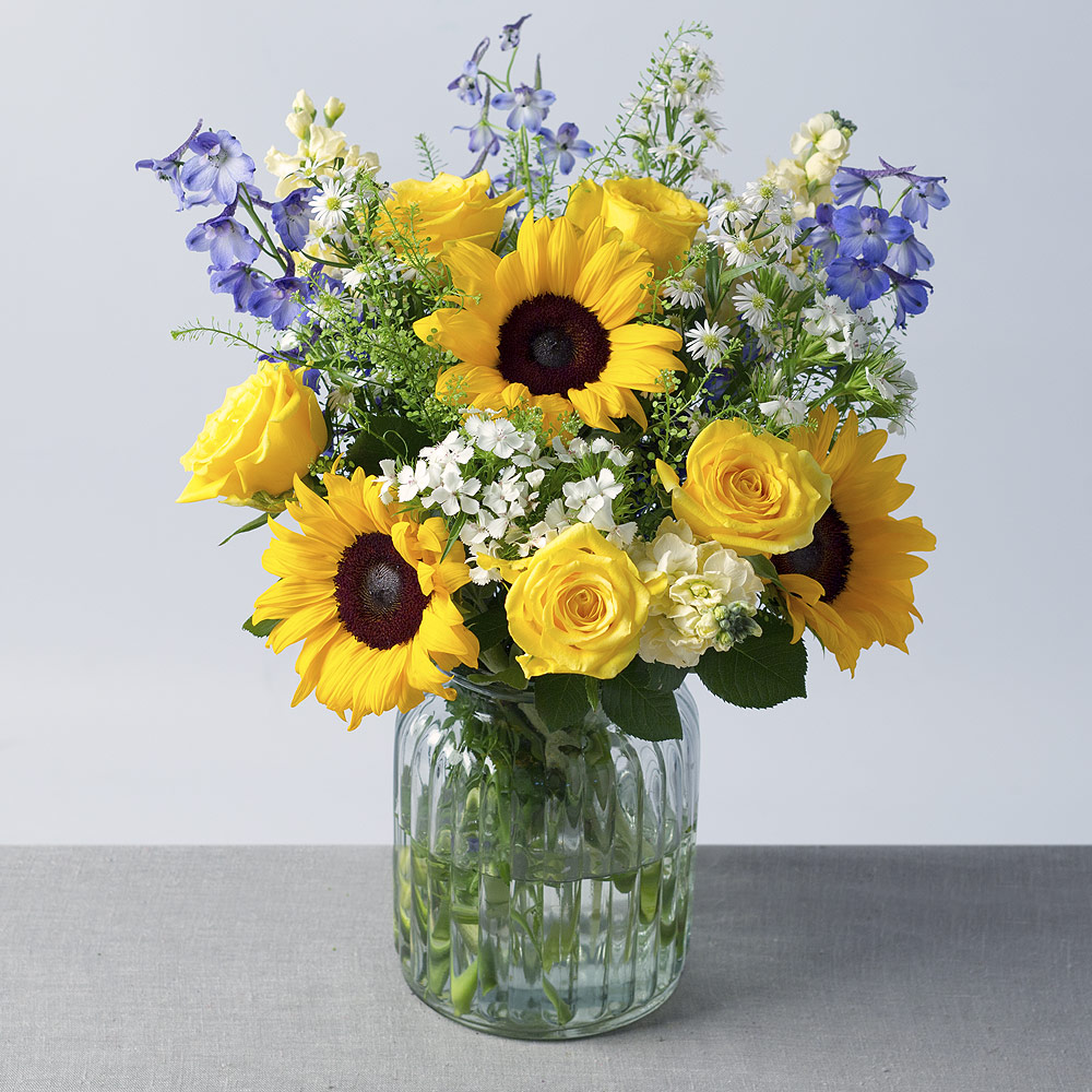 Image of Bold Yellow Moonwalk Roses, pretty white Stocks and stunning Sunflowers star in this wonderful summer bouquet.