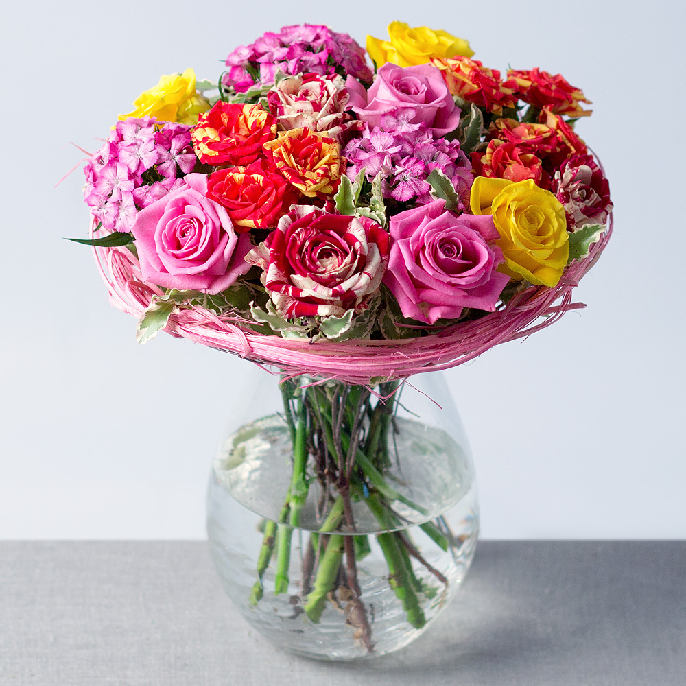 Image of Beautiful Roses in colours of orange, yellow and pink are surrounded by clusters of delicate purple Sweet William, resulting in a simply stunning summer arrangement.Framed with green foliage and presented in a lovely rattan holder, this posy needs no arranging and will make a wonderful gift for a loved one.