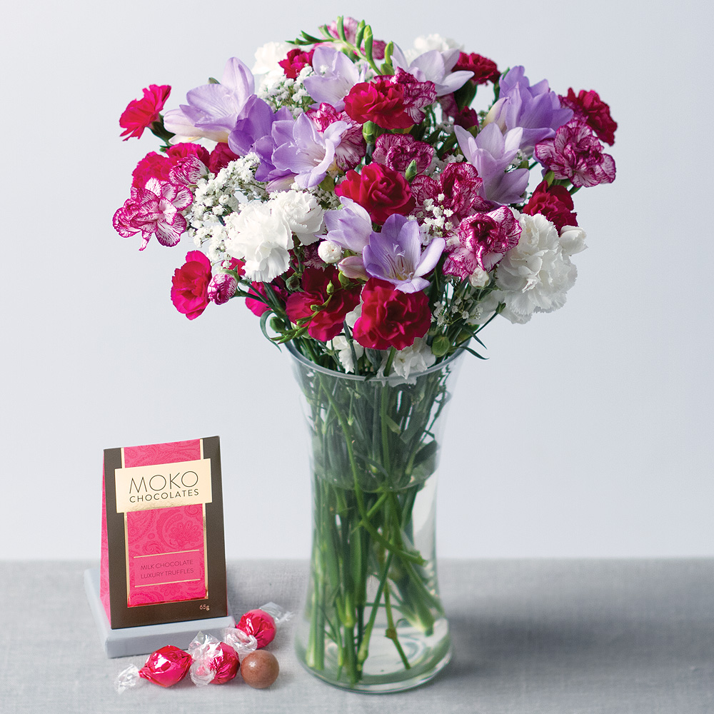 Image of A gorgeous feminine bouquet including white Alstroemeria, two-tone pink and white Carnations, pink Spray Carnations and delicate white Gypsophila.A delicious 110g box of Belgian dusted truffles makes the gift extra special.