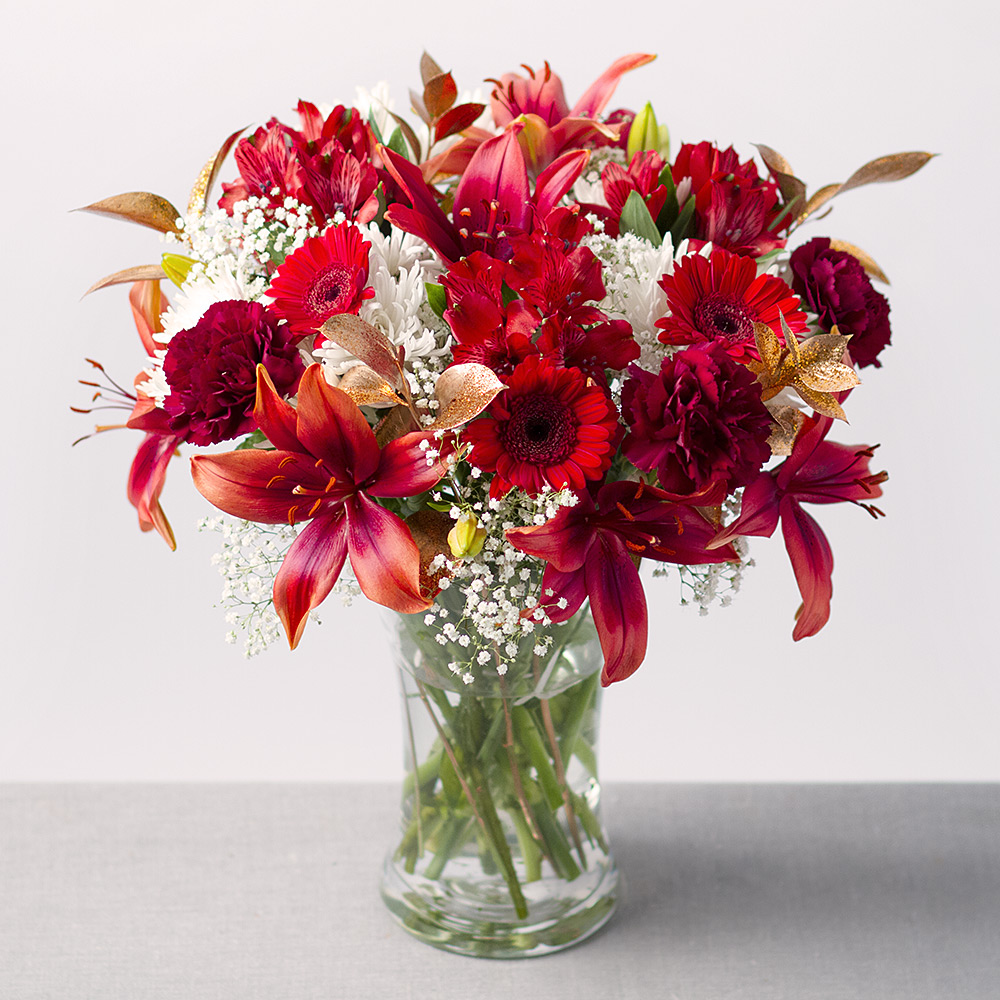 Image of A gorgeous display featuring a mix of red Lilies, Germini and Carnations alongside white Chrysanthemums and Gypsophila.