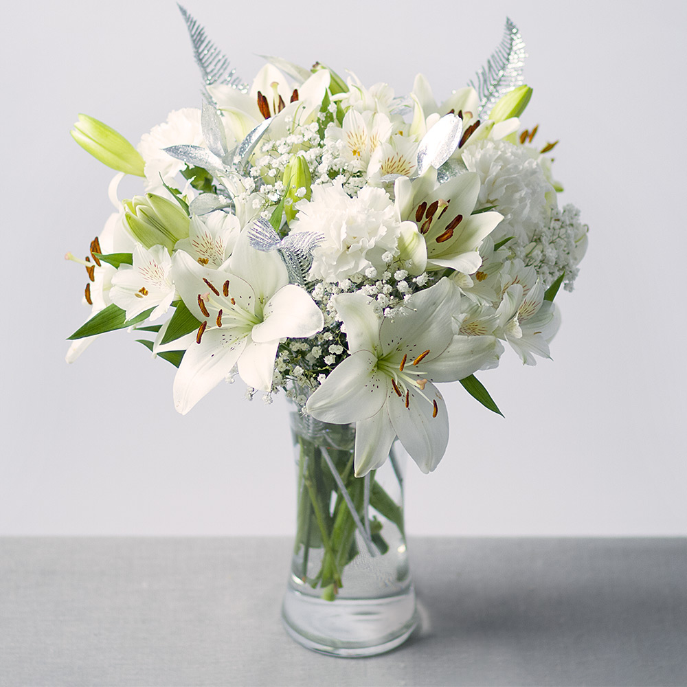Image of Snow white blooms are surrounded by hints of silver to make a lovely contemporary Christmas gift.White Asiatic Lilies, Carnations and Alstroemeria are joined by white Gypsophila and silver Feather and glittered Ruscus leaves.