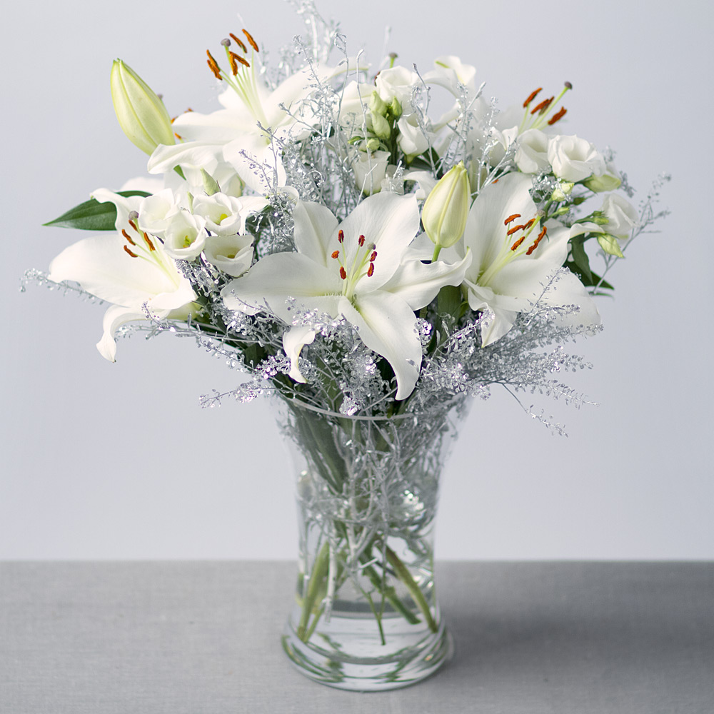 Image of A gorgeous Christmas bouquet containing dramatic white Asiatic Lilies and pretty white Lisianthus .Silver Green Bell foliage and branches of white Birch also feature.